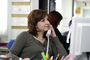 Smiling office worker holding a telephone while staring at her computer