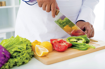 Culinary student holding a sharp kitchen knife and chopping vegetable slices